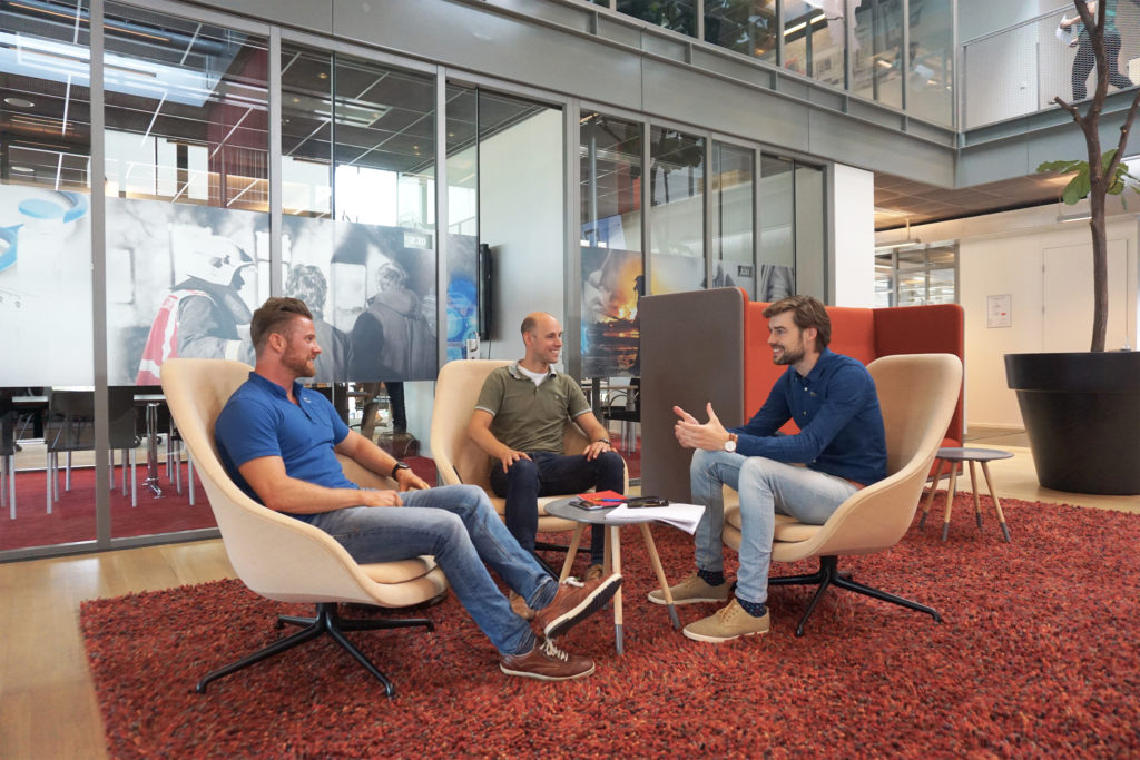 drie mannen overleggen op stoel