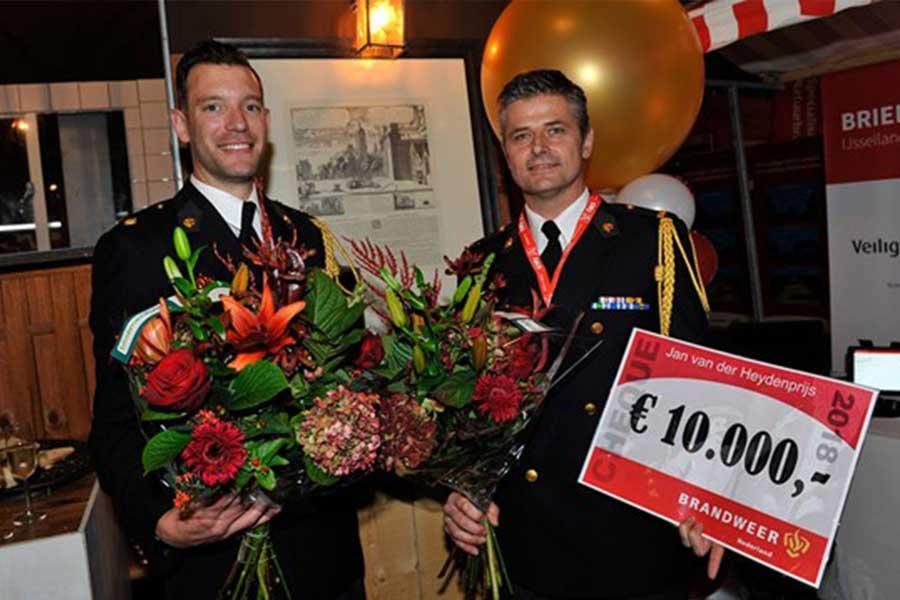 twee brandweermannen met bloemen en voucher 10.000 euro in de hand