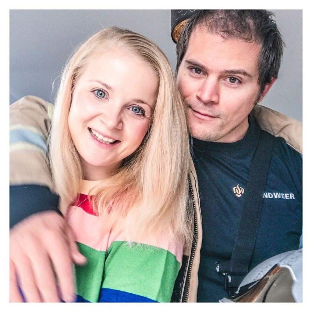 blonde vrouw die door brandweerman omhelst wordt kijkend in de camera